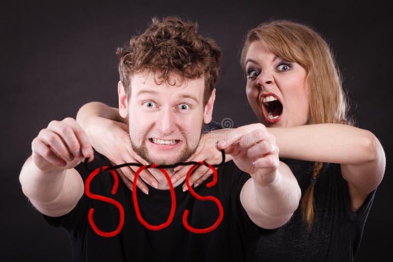 Giovani coppie con cuore rotto e la parola di SOS immagini stock libere da diritti