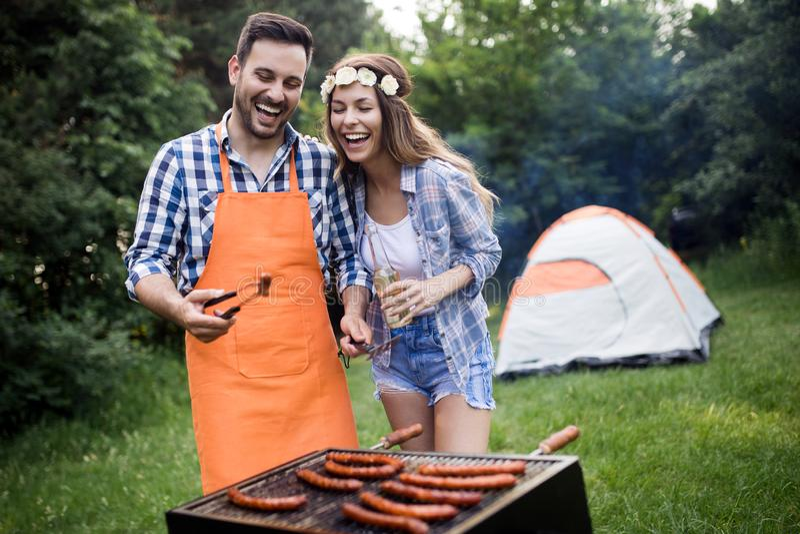 Giovani coppie con i sorrisi e la fabbricazione degli amici del barbecue arrostito in campeggio immagini stock libere da diritti