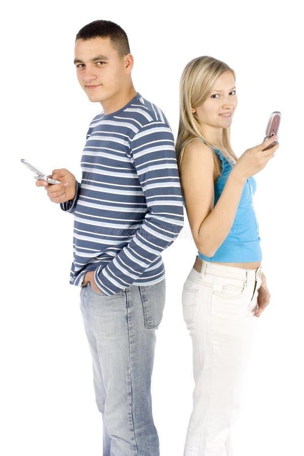 Giovani coppie con i telefoni mobili fotografia stock