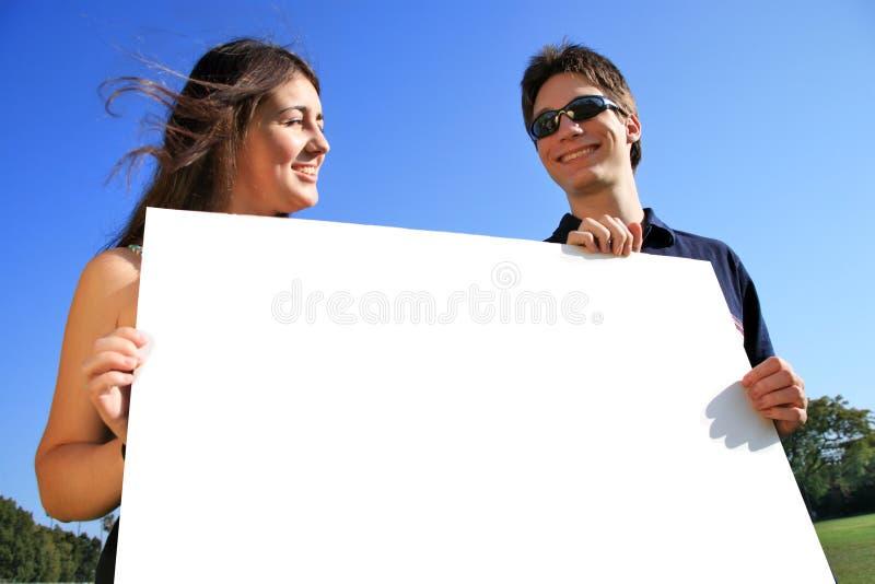 Giovani coppie con il segno in bianco fotografia stock libera da diritti
