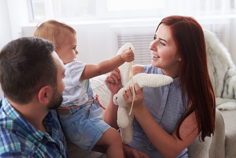 Giovani coppie con la figlia graziosa che gioca sul sofà immagine stock