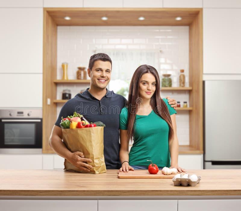 Giovani coppie con le drogherie che cucinano in una cucina immagini stock