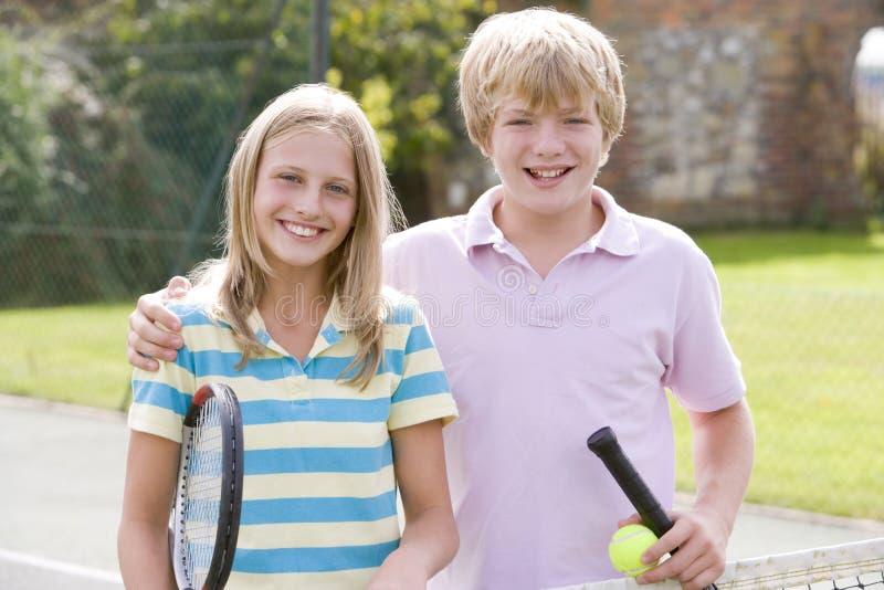 Giovani coppie con le racchette sul sorridere della corte di tennis fotografie stock libere da diritti