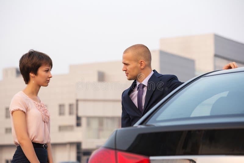 Giovani coppie in conflitto che parla accanto ad un'automobile sulla via della città fotografia stock libera da diritti