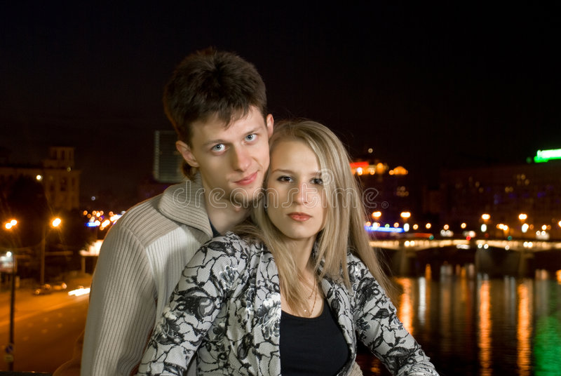 Giovani coppie contro la città di notte fotografia stock