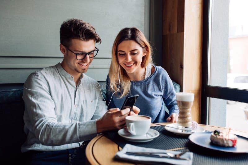 Giovani coppie in cuffia, facendo uso di uno smartphone, spendente tempo al caffè fotografie stock