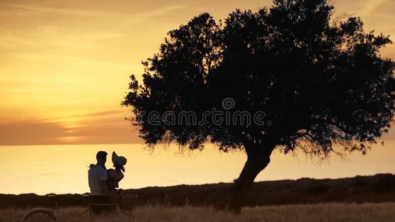 Giovani coppie degli amanti nel tramonto sui precedenti dell'oceano fotografia stock