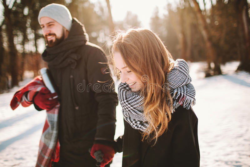 Giovani coppie dei pantaloni a vita bassa che camminano in mani dell'azienda forestale di inverno fotografia stock
