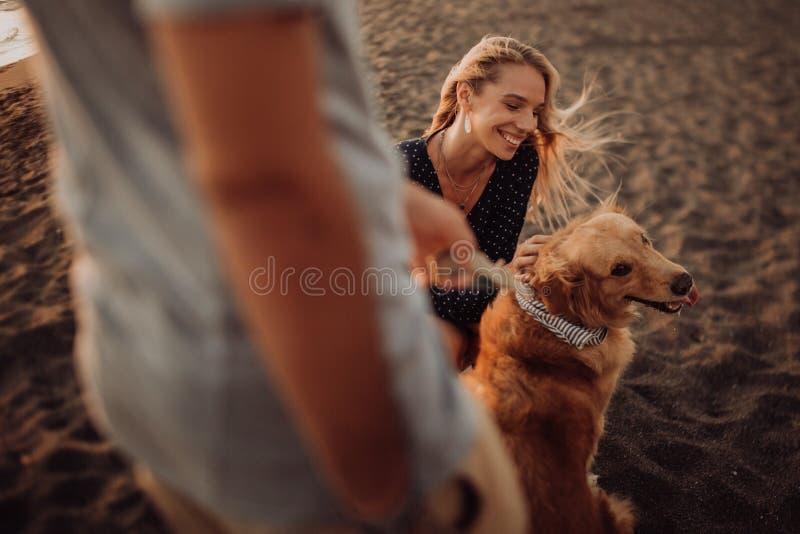 Giovani coppie dei pantaloni a vita bassa di bella risata felice con il golden retriever sulla spiaggia oceano una sabbia Onde co fotografie stock libere da diritti