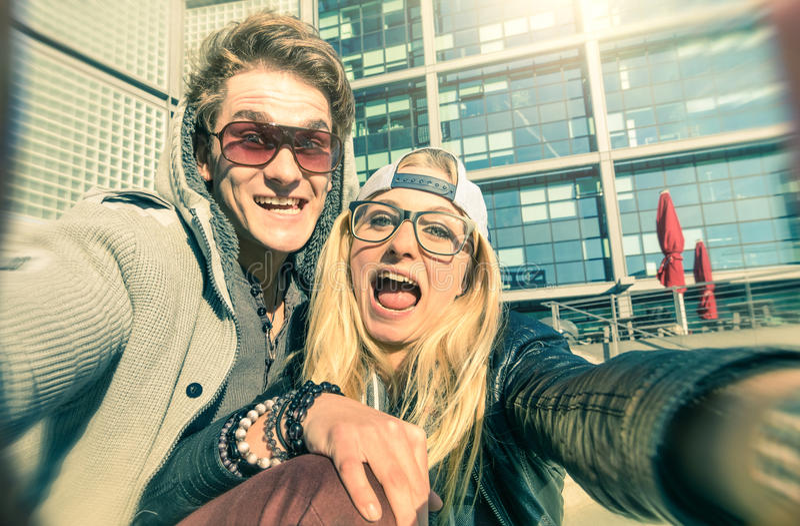 Giovani coppie dei pantaloni a vita bassa nell'amore che prende un selfie divertente nell'area urbana fotografia stock