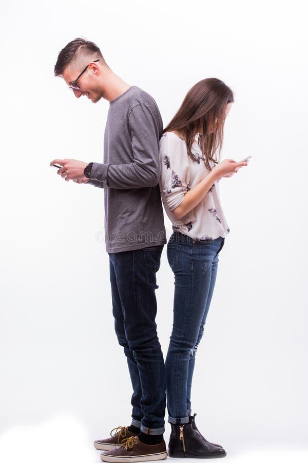 Giovani coppie dei pantaloni a vita bassa nell'amore che si trascura con i telefoni fotografia stock