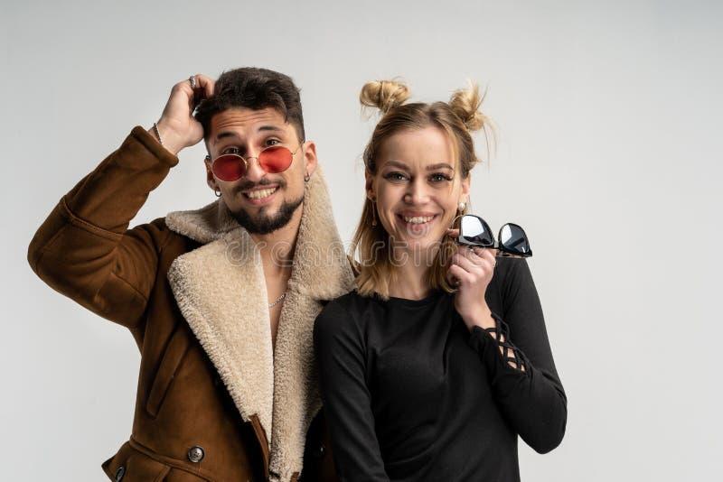 Giovani coppie dell'uomo barbuto in cappotto ed in donna graziosa in vestito nero con capelli biondi lunghi fotografia stock libera da diritti