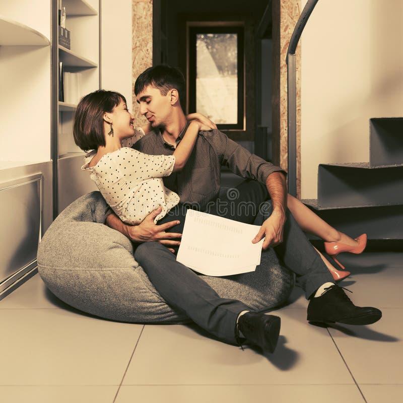 Giovani coppie di affari che flirtano nel carbone all'ufficio fotografie stock libere da diritti
