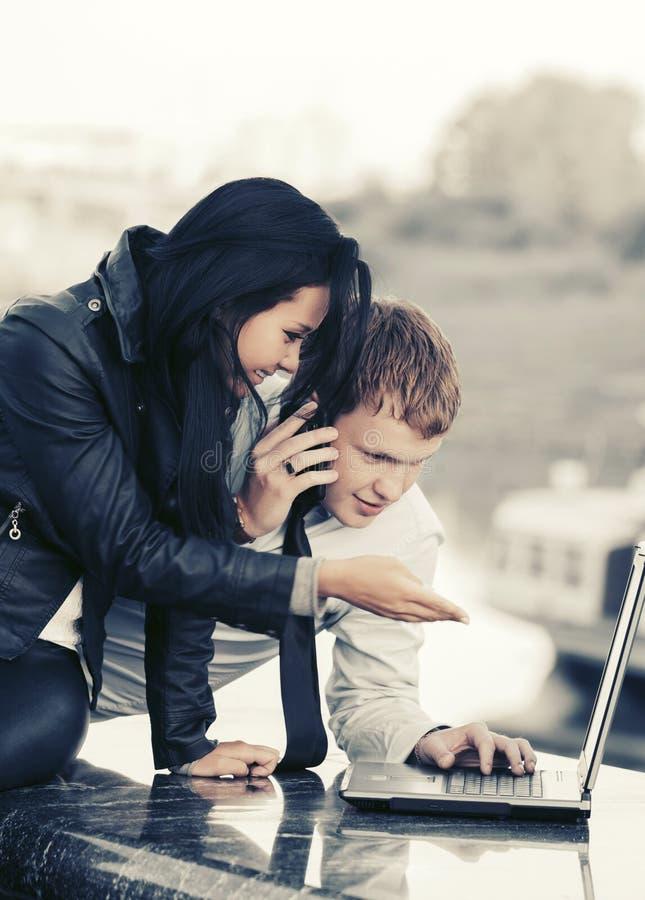 Giovani coppie di affari di modo facendo uso del computer portatile all'aperto fotografia stock