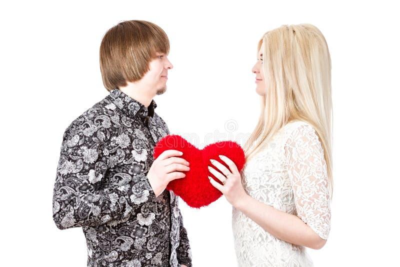 Giovani coppie di amore che tengono il cuore del biglietto di S. Valentino rosso fotografie stock libere da diritti