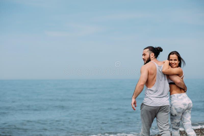 Giovani coppie di forma fisica che abbracciano stare sulla spiaggia, esaminante orizzonte fotografia stock libera da diritti
