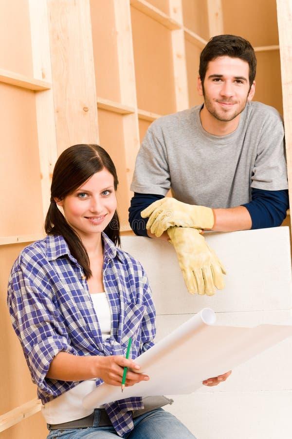 Giovani coppie di miglioramento domestico con le cianografie fotografie stock
