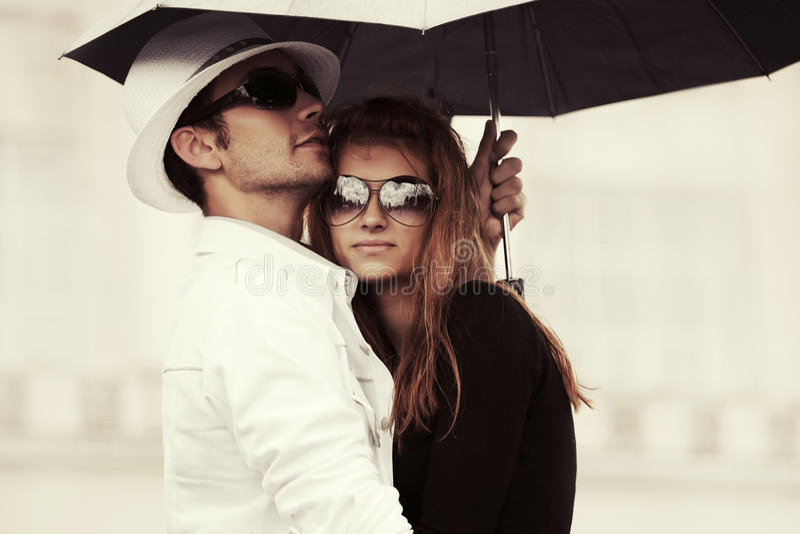 Giovani coppie di modo nell'amore con l'ombrello in via della città fotografie stock libere da diritti