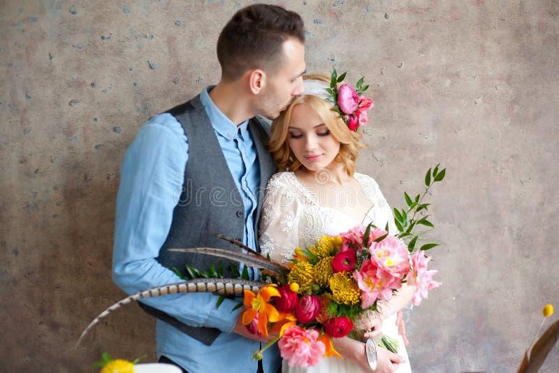 Giovani coppie di nozze contro la parete di struttura fotografia stock