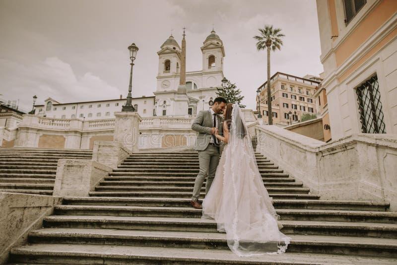Giovani coppie di nozze sulle scale spagnole a Roma fotografia stock