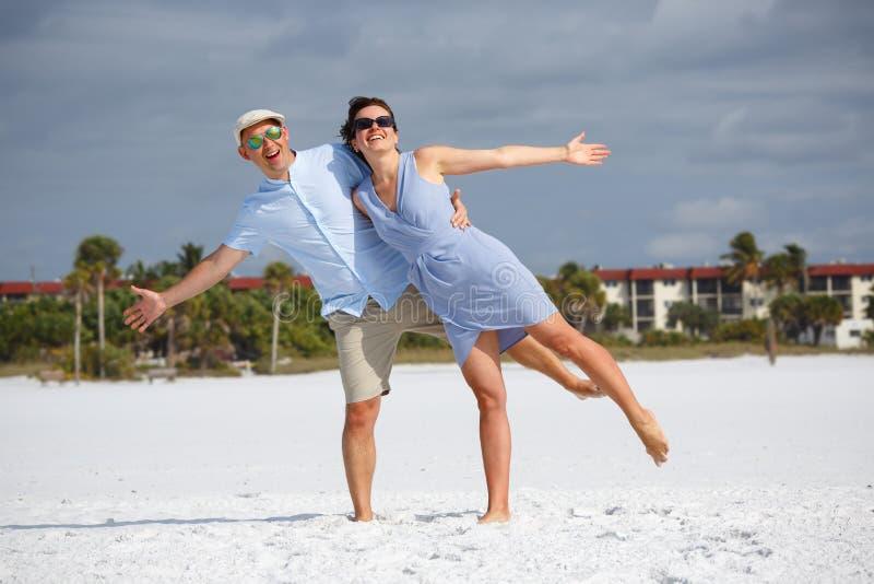 Giovani coppie divertendosi alla spiaggia tropicale immagini stock