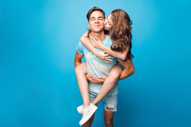 Giovani coppie divertendosi sul fondo blu in studio La ragazza graziosa con capelli ricci lunghi sta guidando sulla parte posteri immagini stock libere da diritti