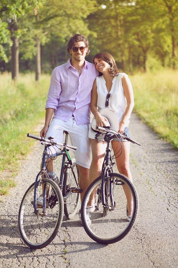 Giovani coppie divertenti con le biciclette fotografie stock
