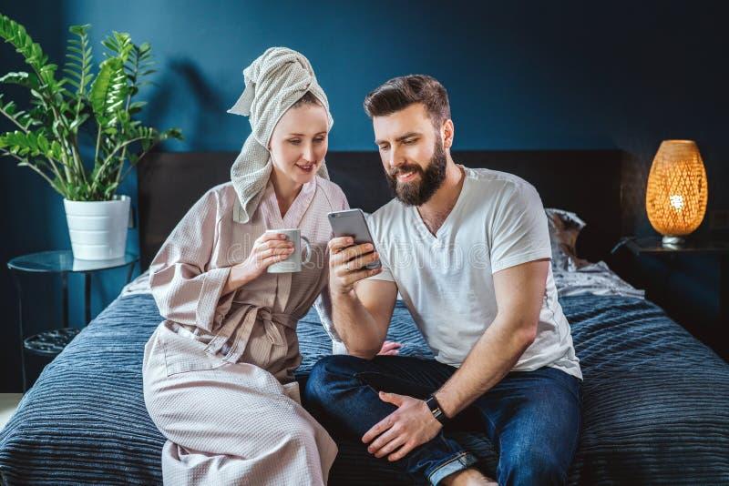 Giovani coppie, donna in accappatoio ed asciugamano sulla sua testa, sedentesi nella camera da letto sul letto L'uomo mostra le i fotografia stock