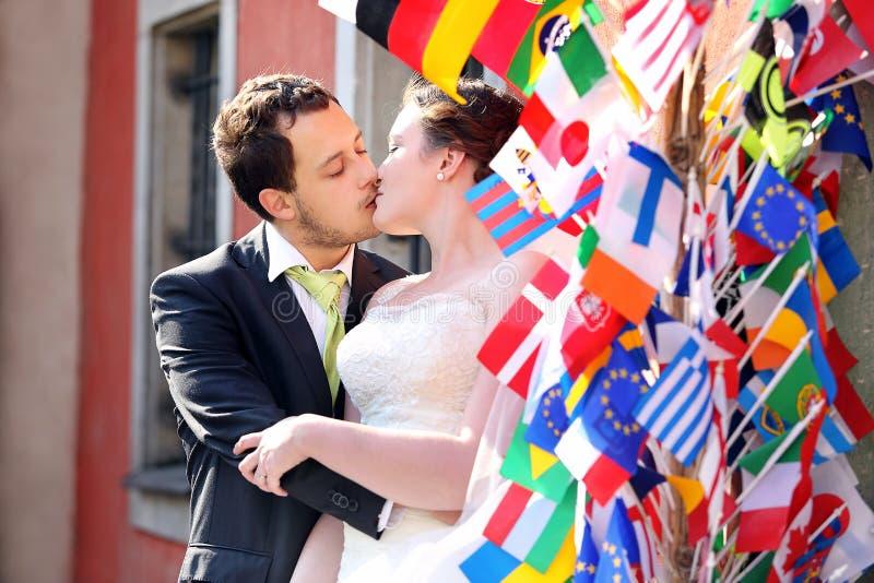 Giovani coppie dopo nozze che baciano in un abbraccio immagini stock