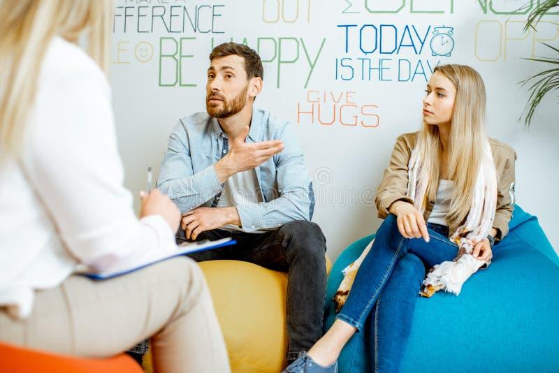 Giovani coppie durante il consiglio psicologico con lo psicologo fotografie stock