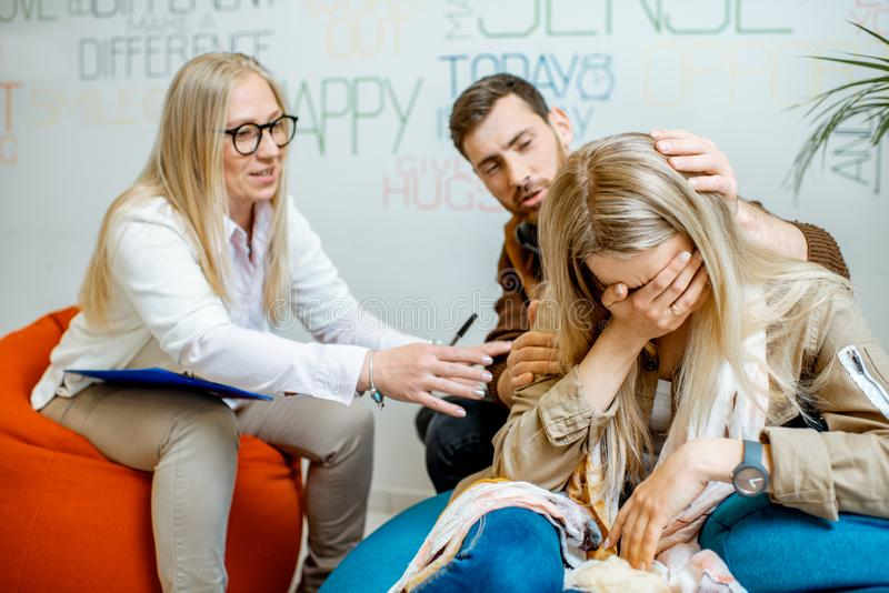 Giovani coppie durante il consiglio psicologico con lo psicologo fotografia stock