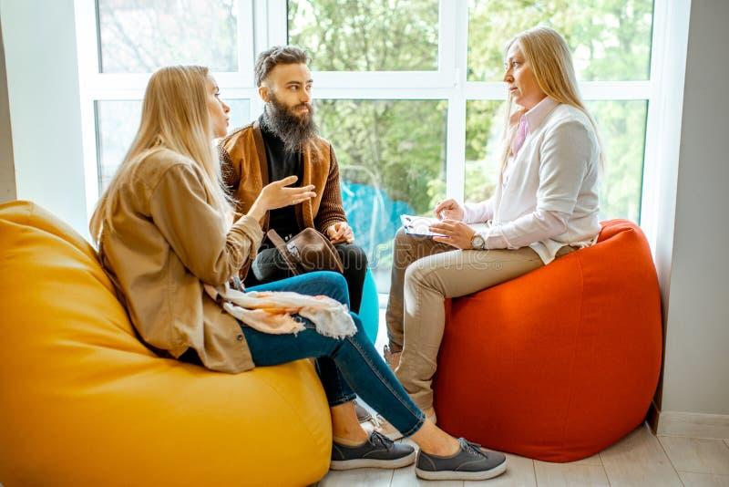 Giovani coppie durante il consiglio psicologico con lo psicologo immagine stock