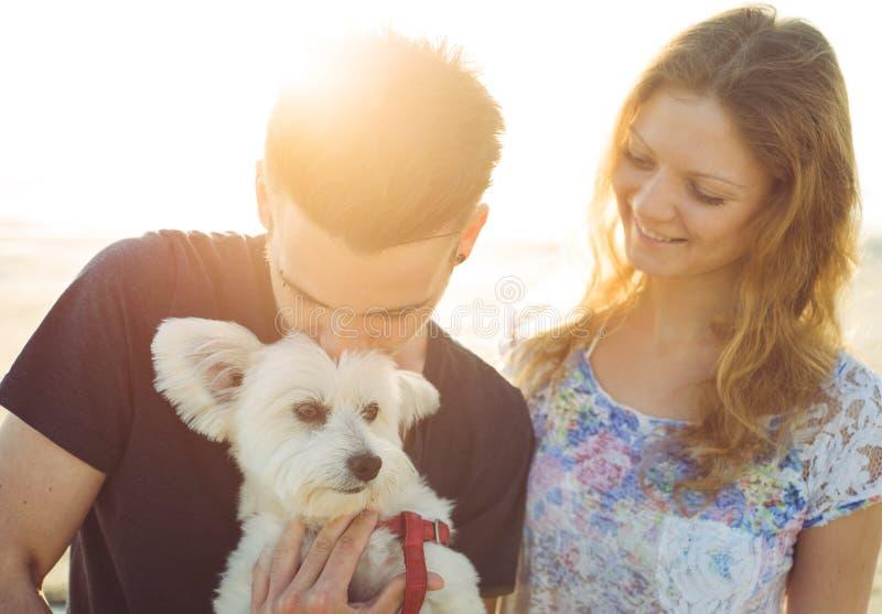 Giovani coppie e cane bianco felicemente insieme fotografia stock libera da diritti