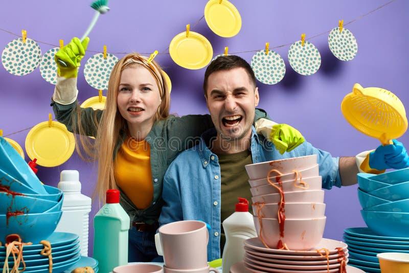 Giovani coppie emozionali pazze divertendosi nella cucina immagine stock