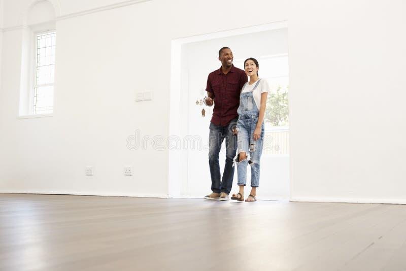 Giovani coppie emozionanti che avvicinano nella nuova casa fotografia stock