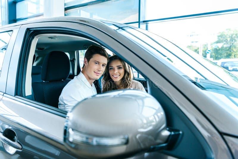 Giovani coppie eterosessuali che si siedono in un'automobile in sala d'esposizione e che sorridono con l'aperto fotografia stock libera da diritti