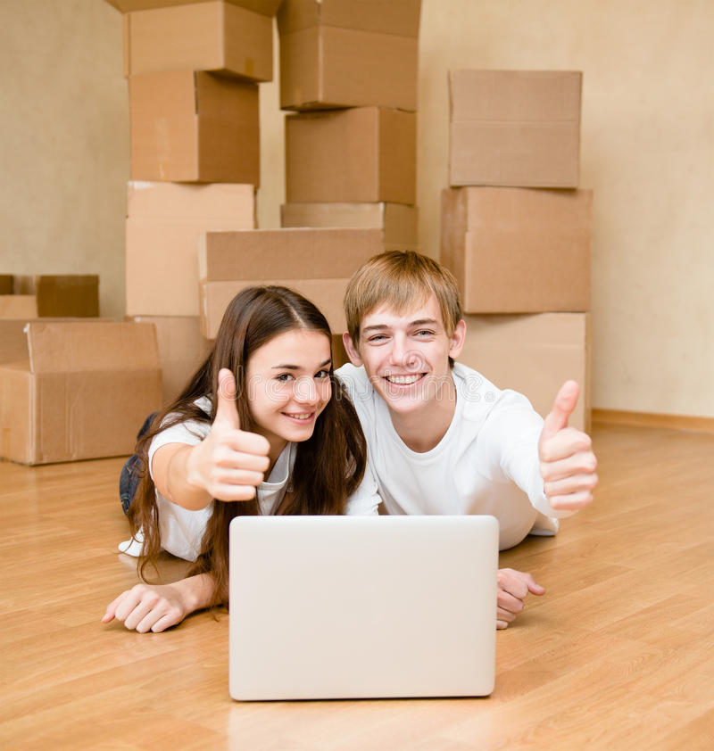 Giovani coppie facendo uso del computer portatile in loro nuovi pollici di mostra e della casa su fotografie stock