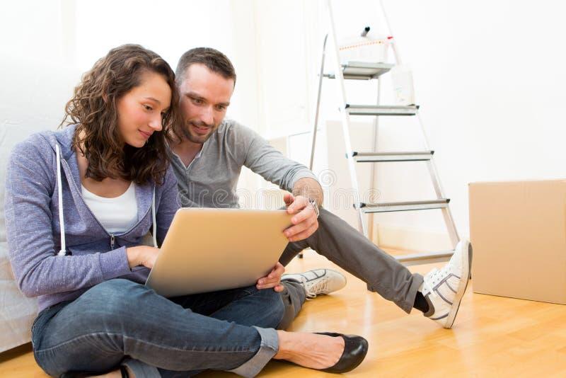 Giovani coppie facendo uso del computer portatile mentre muovendosi nel nuovo piano immagini stock