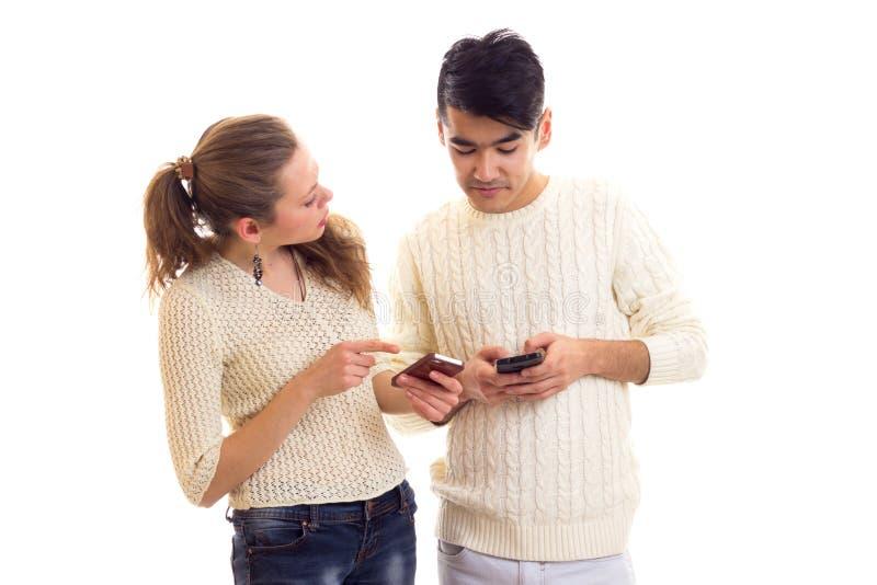 Giovani coppie facendo uso dello smartphone fotografia stock