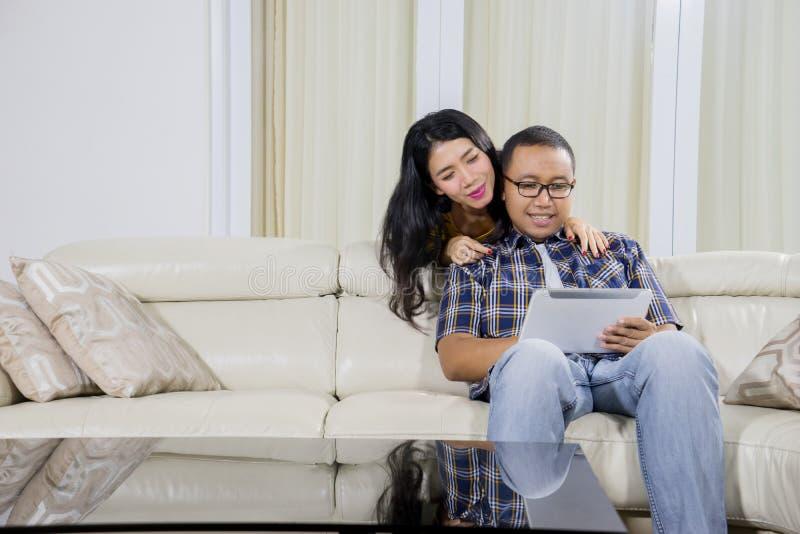 Giovani coppie facendo uso di una compressa digitale a casa immagine stock