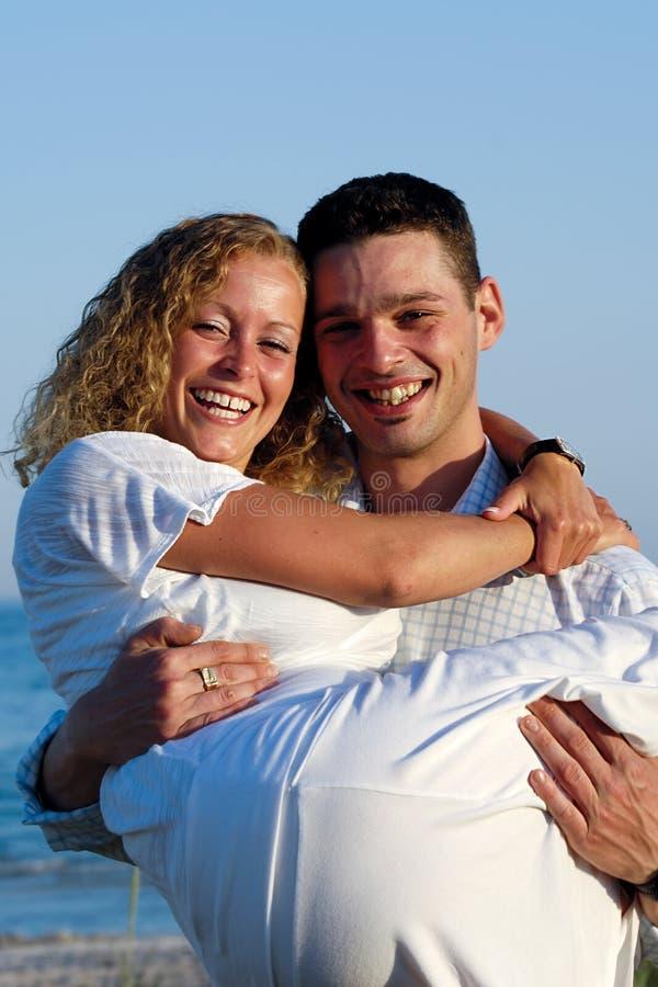 Giovani coppie felici alla spiaggia immagini stock