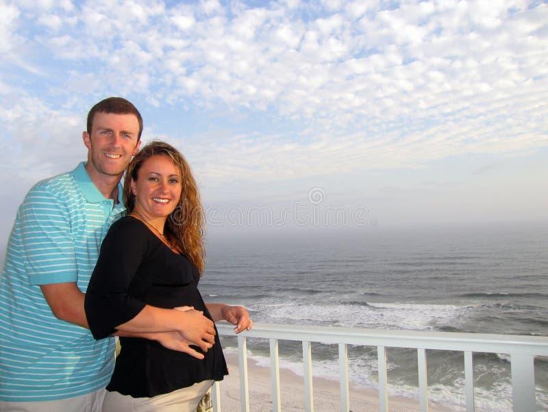 Giovani coppie felici alla spiaggia fotografia stock