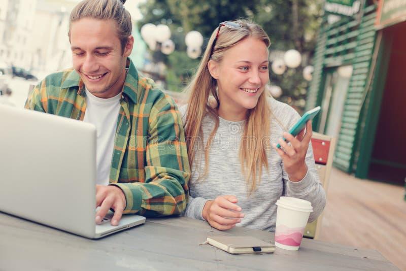 Giovani coppie felici in caffè della via, facendo uso del telefono e del computer portatile fotografie stock