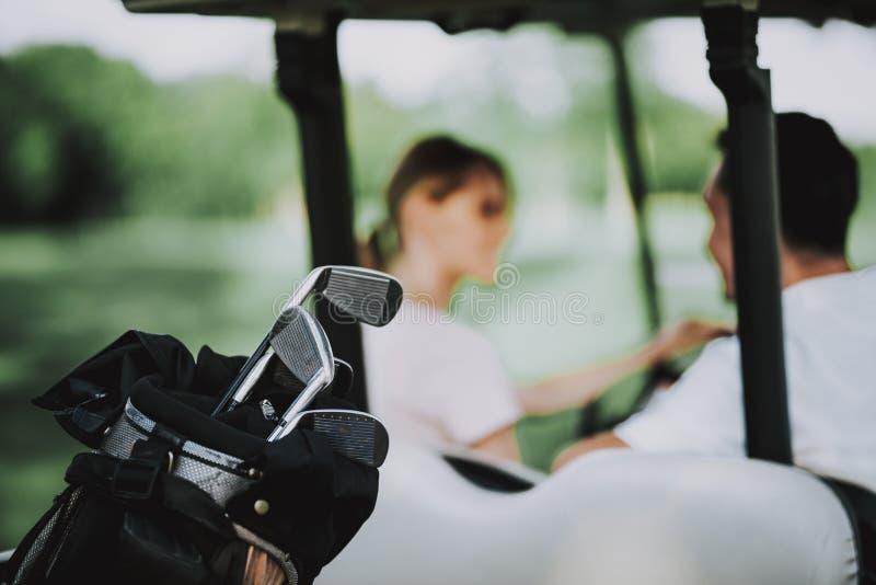 Giovani coppie felici in carretto bianco sul campo di golf immagini stock