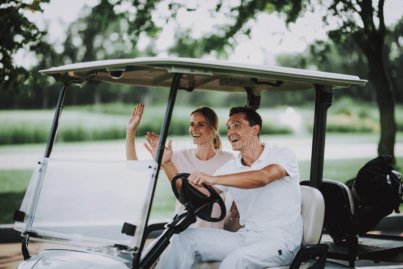 Giovani coppie felici in carretto bianco sul campo di golf fotografia stock libera da diritti
