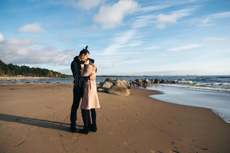 Giovani coppie felici che abbracciano e che baciano sulla spiaggia Tempo freddo di autunno, alberi nei precedenti fotografia stock