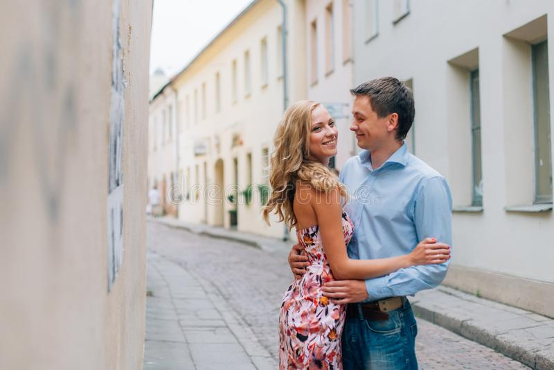 Giovani coppie felici che abbracciano sulla via immagini stock