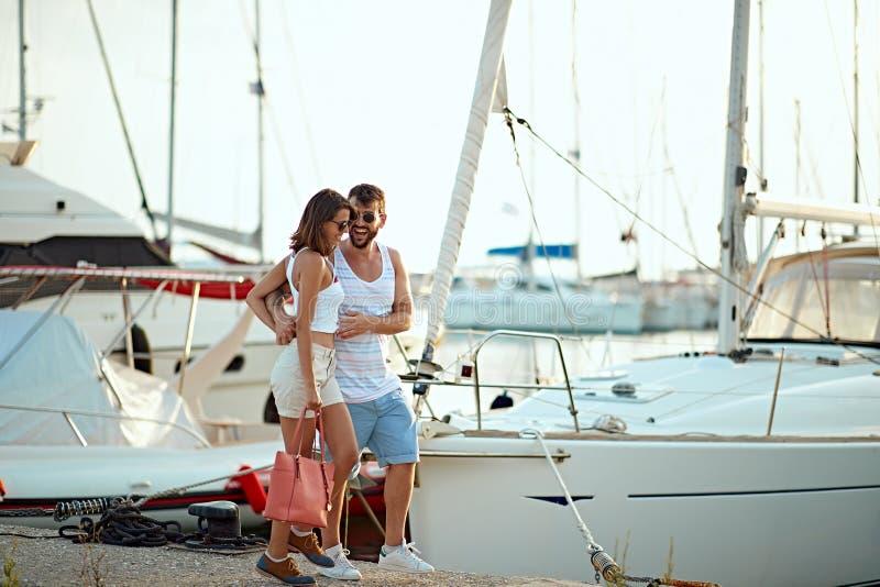 Giovani coppie felici che camminano dal porto di una località di soggiorno turistica del mare con le barche a vela fotografie stock
