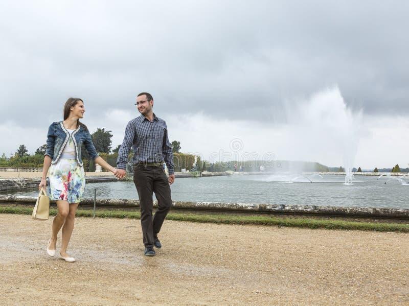 Giovani coppie felici che camminano in un giardino francese fotografia stock
