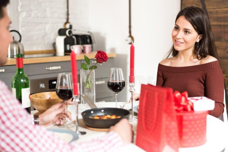 Giovani coppie felici che celebrano giorno del ` s del biglietto di S. Valentino con una cena a casa fotografia stock libera da diritti
